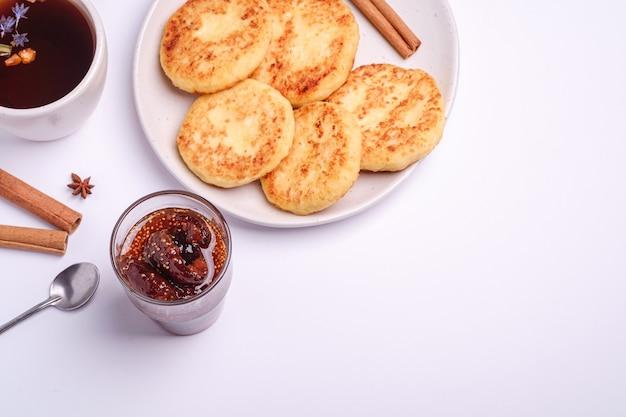 Frittelle di ricotta con marmellata di fichi e tè caldo aromatico nero, atmosfera per la colazione di natale con anice e cannella su sfondo bianco, vista angolare
