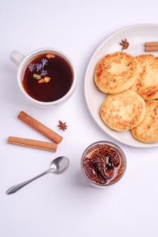 Frittelle di ricotta con marmellata di fichi e tè caldo aromatico nero, atmosfera per la colazione di natale con anice e cannella su sfondo bianco, vista dall'alto