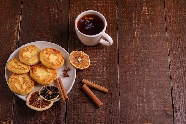 Frittelle di ricotta con tè aromatico nero caldo, atmosfera per la colazione di natale con anice, cannella e agrumi secchi su sfondo di legno, vista angolare