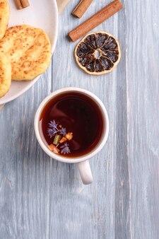 Frittelle di ricotta con tè aromatico nero caldo, atmosfera per la colazione di natale con anice, cannella e agrumi secchi su fondo di legno, vista dall'alto