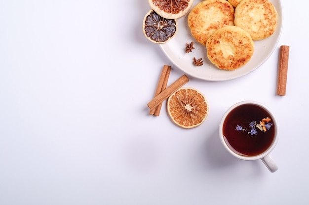 Frittelle di ricotta con tè aromatico nero caldo, atmosfera per la colazione di natale con anice e cannella su sfondo bianco, spazio copia vista dall'alto