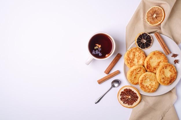 Frittelle di ricotta con tè aromatico nero caldo, atmosfera per la colazione di natale con anice e cannella su sfondo bianco, vista dall'alto