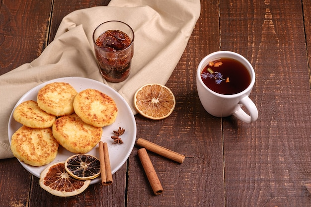 Frittelle di ricotta con tè aromatico nero caldo con marmellata di fichi, atmosfera per la colazione di natale con anice, cannella e agrumi secchi su sfondo di legno, vista angolare
