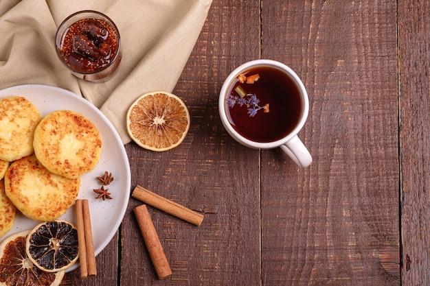 Frittelle di ricotta con tè aromatico nero caldo con marmellata di fichi, atmosfera da colazione natalizia con anice, cannella e agrumi secchi su sfondo di legno, vista dall'alto