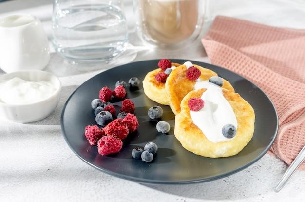 Frittelle di ricotta su un piatto nero con frutti di bosco, panna, marmellata e tazza di latte.