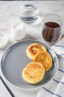 Frittelle di ricotta su un piatto nero con panna, marmellata e tazza di latte. colazione salutare. cibo fatto in casa