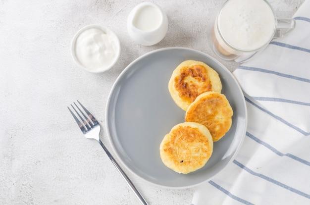 Frittelle di ricotta su un piatto nero con panna, marmellata e tazza di latte. sano