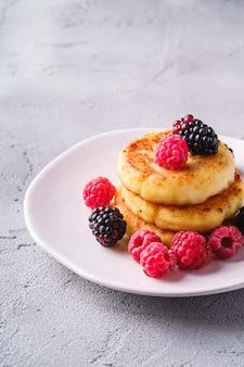 Frittelle di ricotta, dessert di frittelle di ricotta con lamponi e bacche di mora nel piatto