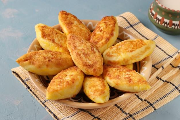 Frittelle di ricotta, syrniki ucraino tradizionale fatto in casa con semolino e tazza di latte su un piatto su una superficie blu chiaro