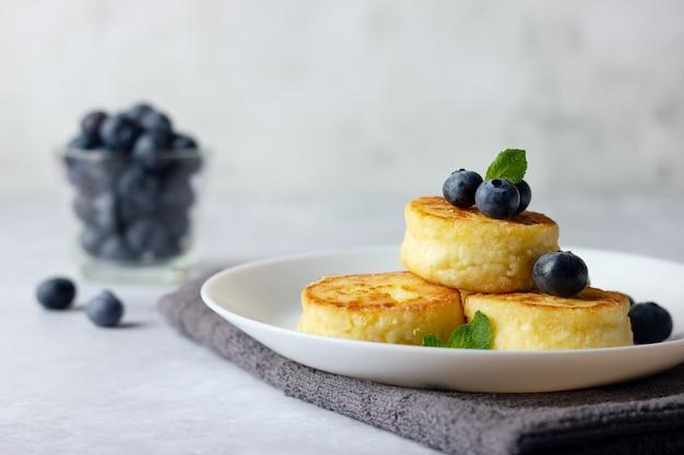 Frittelle di ricotta, syrniki, frittelle di ricotta con mirtilli freschi su sfondo chiaro. menu della colazione russa.