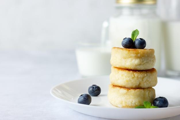 Frittelle di ricotta, syrniki, frittelle di ricotta con mirtilli freschi e latte su sfondo chiaro. copia spazio per il tuo testo. menu della colazione russa.