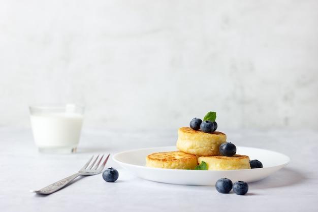 Frittelle di ricotta, syrniki, frittelle di ricotta con mirtilli freschi e latte su sfondo chiaro.