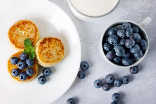 Frittelle di ricotta, syrniki con mirtilli in un piatto bianco.