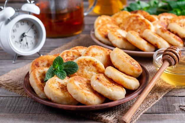 Frittelle di ricotta, syrniki con miele su un piatto su fondo di legno. prima colazione