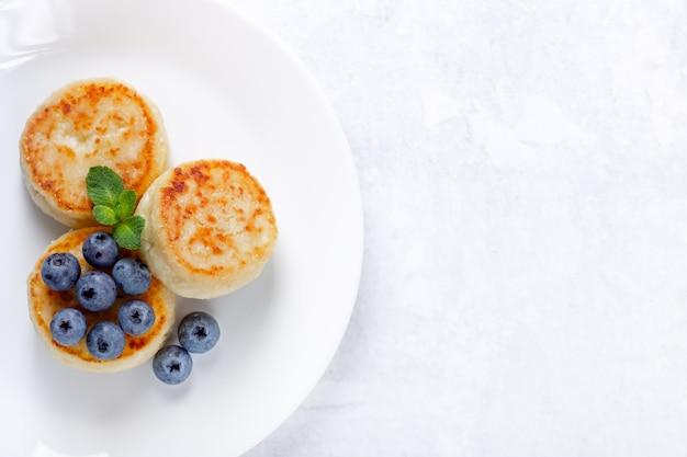 Frittelle di ricotta con mirtilli su sfondo bianco, colazione o pranzo. copia spazio per il tuo testo.