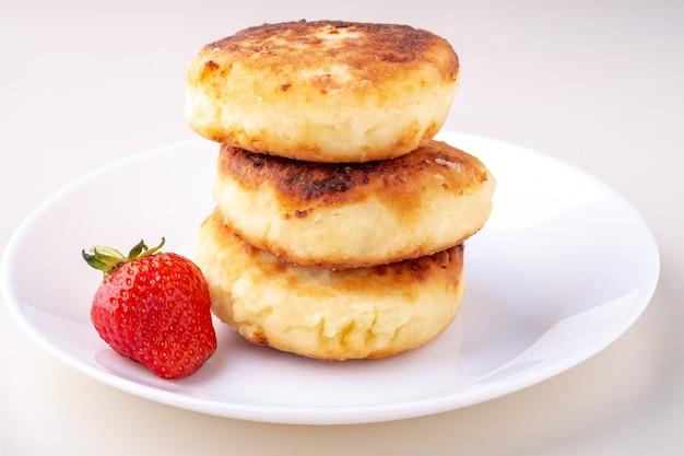 Pancake della ricotta con una fragola sulla vista di angolo isolata piatto bianco