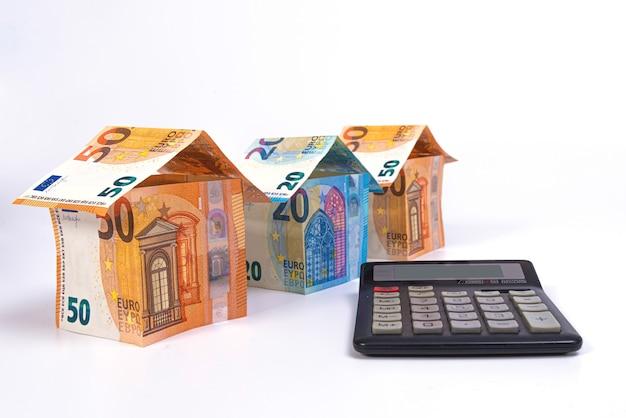 Cottage fatti di banconote da 50 e 20 euro e una calcolatrice isolata su una superficie chiara, primo piano