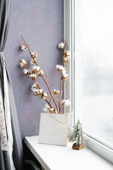 Rami di cotone in un vaso alla finestra. decorazioni natalizie in casa. capodanno e inverno accoglienti