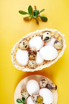 Fiori di cotone e uova di quaglia in un piccolo cesto e piatto sulla trama del panno