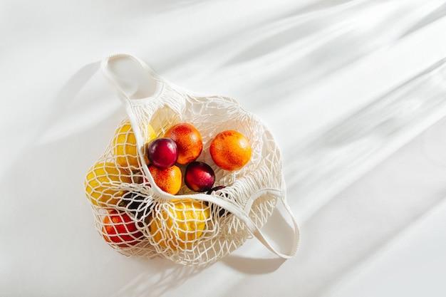 Borsa in rete di cotone con frutta. stile di vita sostenibile. concetto ecologico.