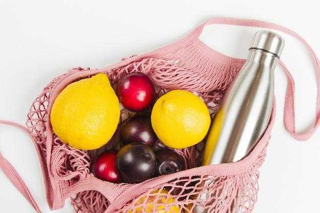 Borsa in rete di cotone con bottiglia d'acqua in metallo riutilizzabile e frutta. stile di vita sostenibile. ecologico