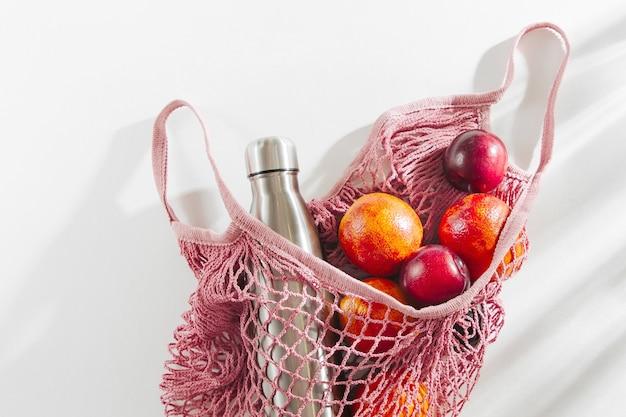 Borsa in rete di cotone con bottiglia d'acqua in metallo riutilizzabile e frutta. stile di vita sostenibile. ecologico Foto Premium