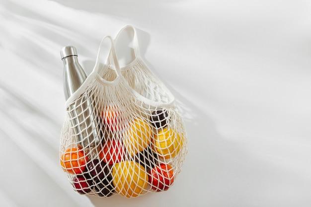 Borsa in rete di cotone con bottiglia d'acqua in metallo riutilizzabile e frutta. stile di vita sostenibile.