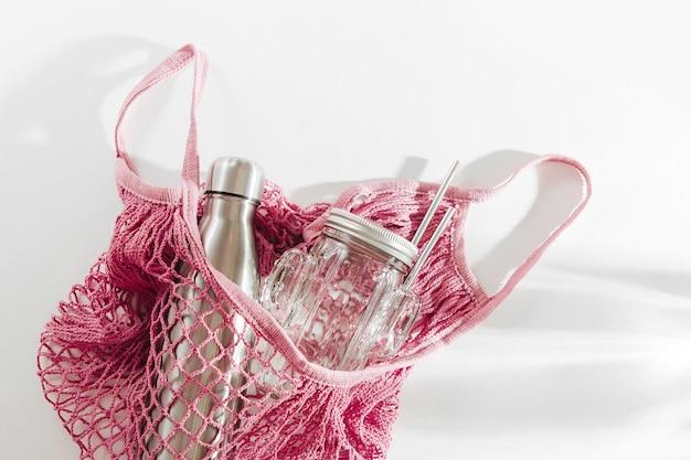 Borsa in rete di cotone con borraccia in metallo riutilizzabile, barattolo di vetro e cannuccia. concetto di spreco zero