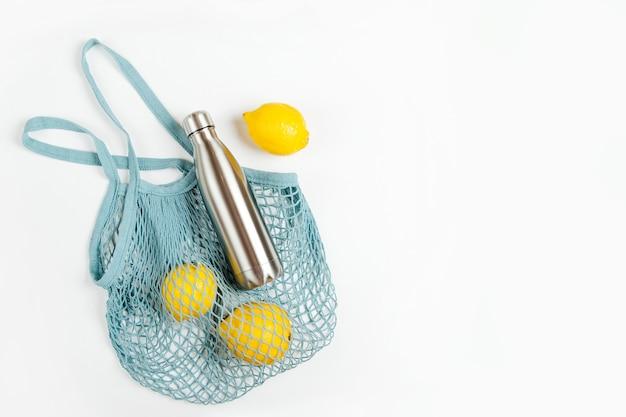 Borsa in rete di cotone con borraccia in metallo riutilizzabile e limoni. stile di vita sostenibile.