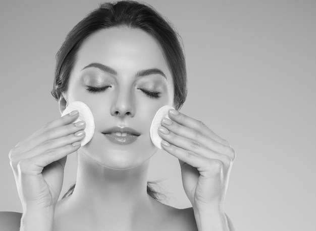 Trucco commovente della pelle pulita del viso della donna del batuffolo di cotone. colpo dello studio. monocromo. grigio. bianco e nero.