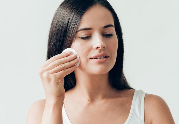 Il viso della donna del batuffolo di cotone rimuove il trucco naturale della pelle sana. colpo dello studio.