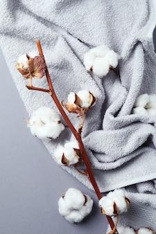 Ramo e asciugamano della pianta del cotone sulla superficie grigia