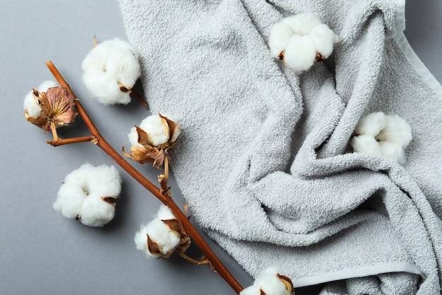 Ramo e asciugamano della pianta del cotone su gray