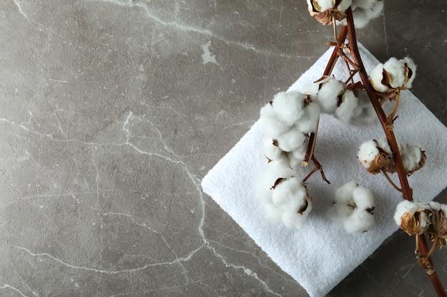 Rami di piante di cotone e asciugamano su grigio