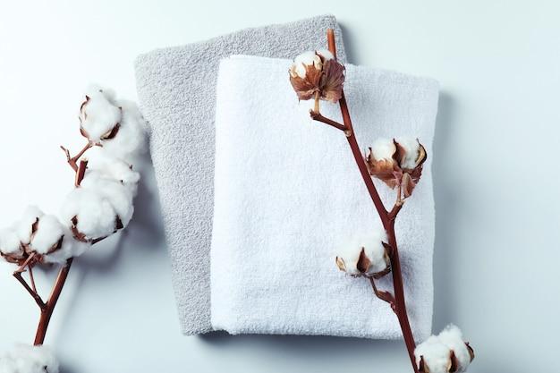 Rami e asciugamani della pianta del cotone sulla superficie bianca