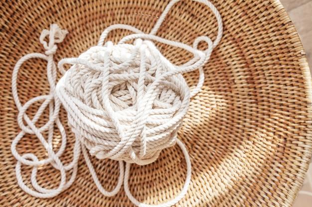 Corda di cotone per macramè fatto a mano in un cestino intrecciato. hobby femminile. copia spazio