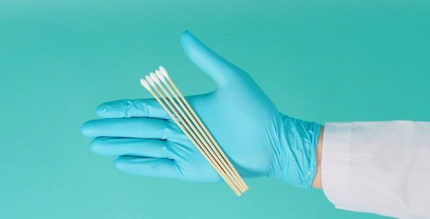 Bastoncini di cotone per tampone in mano con camice da medico e guanti medici blu o guanto in lattice su sfondo verde menta o tiffany blue. concetto covid-19