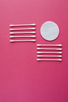 Tamponi di cotone e dischi isolati su uno sfondo rosa. prodotti per l'igiene