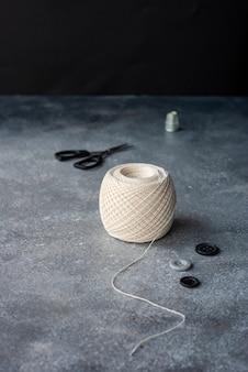 Bobina di filo di cotone bianco per maglieria, bottoni e forbici su un tavolo grigio scuro