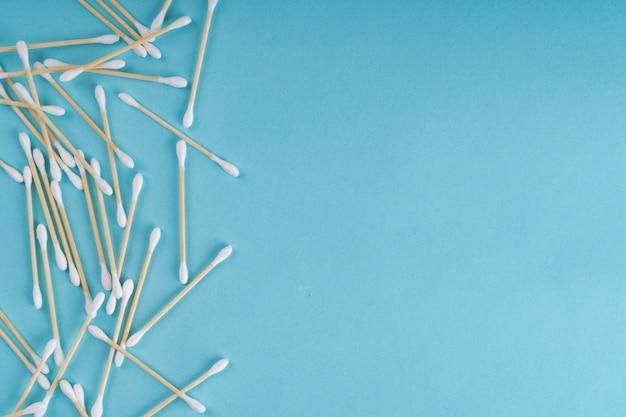 Tamponi di legno dell'orecchio di cotone su fondo blu. vista dall'alto. ecologico, nessuna plastica