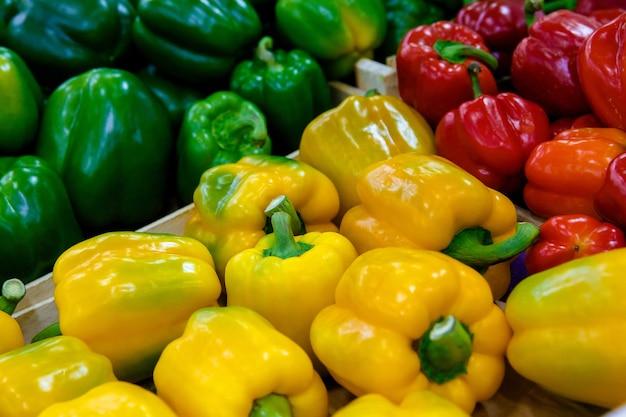 Contatore o vetrina con peperoni gialli, verdi e rossi nel mercato