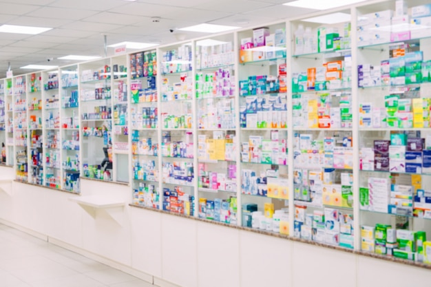 Prodotti farmaceutici della medicina dello spazio in bianco del farmaco della farmacia del negozio medico della droga del fuoco della sfuocatura dello scaffale del fondo della farmacia del contatore.
