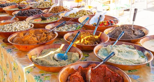 Il bancone con olive e olio d'oliva sul mercato.