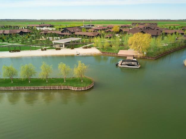 Country club o villaggio sulla riva di un laghetto artificiale. vita e riposo in campagna. paesaggio primaverile. vista dall'alto.