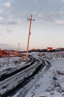 Strada sterrata di campagna con pozzanghere fangose e neve che si scioglie all'inizio della primavera al tramonto.