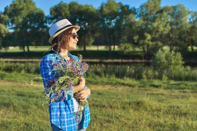 Ritratto di campagna di una bella donna adulta con cappello con bouquet di fiori di campo. paesaggio naturale verde, prati primaverili estivi, la femmina distoglie lo sguardo, copia spazio