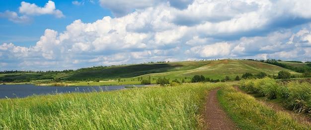 Una strada di campagna tra campi erbosi, vicino a un lago e colline