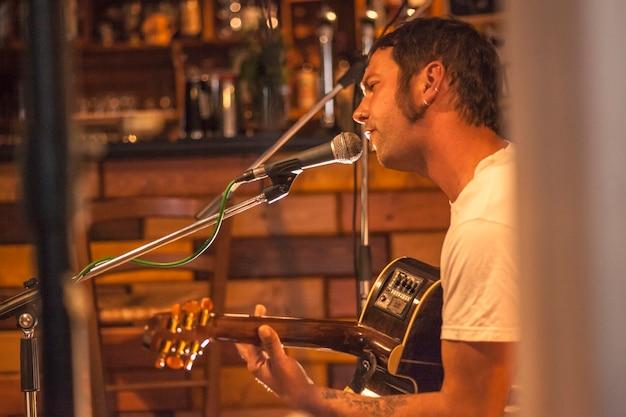 Il cantante country canta in un bar sotto le luci soffuse