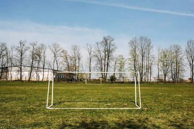 Cancello di calcio di calcio del paese sul campo verde vuoto