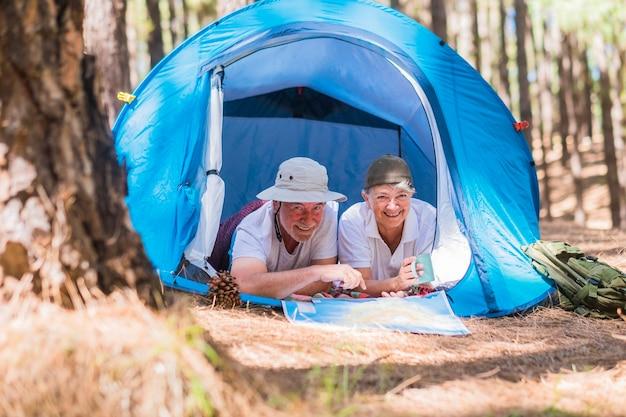 Un paio di persone anziane che viaggiano attive si divertono insieme all'interno di una tenda in un campeggio libero nella foresta